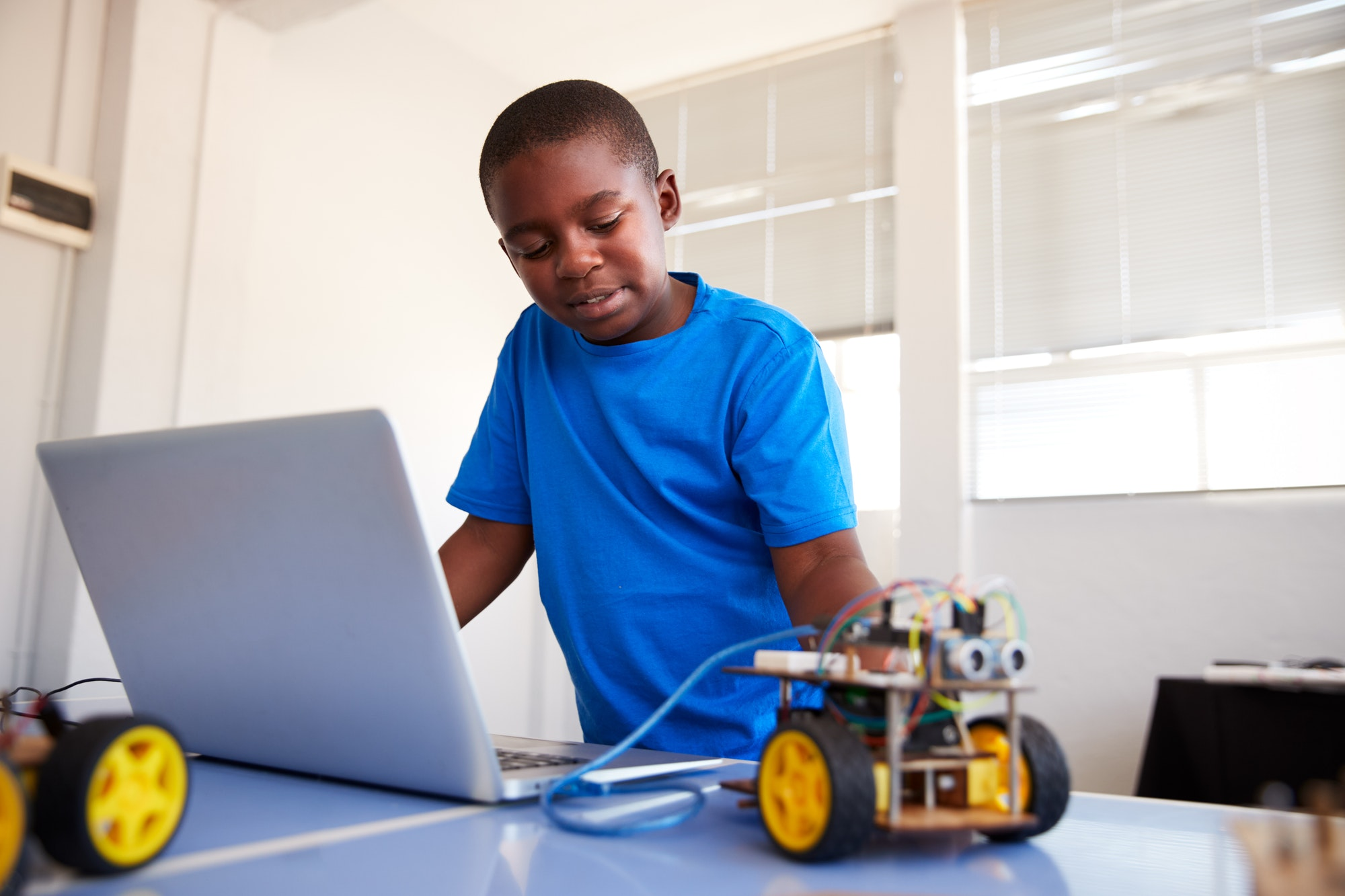 Male Student Building And Programing Robot Vehicle In After School Computer Coding Class