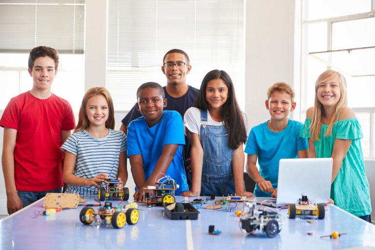 Portrait Of Students With Teacher Building Robot Vehicle In After School Computer Coding Class