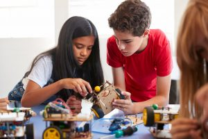Two Students In After School Computer Coding Class Building And Learning To Program Robot Vehicle