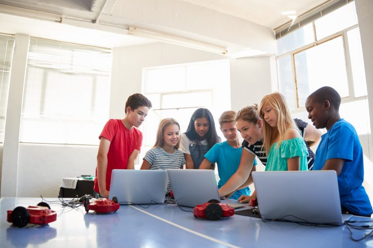 Group Of Students In After School Computer Coding Class Learning To Program Robot Vehicle