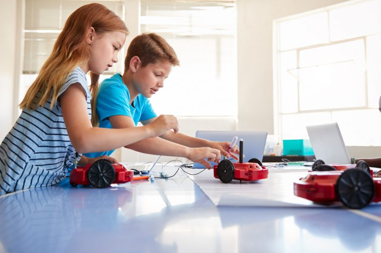Two Students In After School Computer Coding Class Learning To Program Robot Vehicle